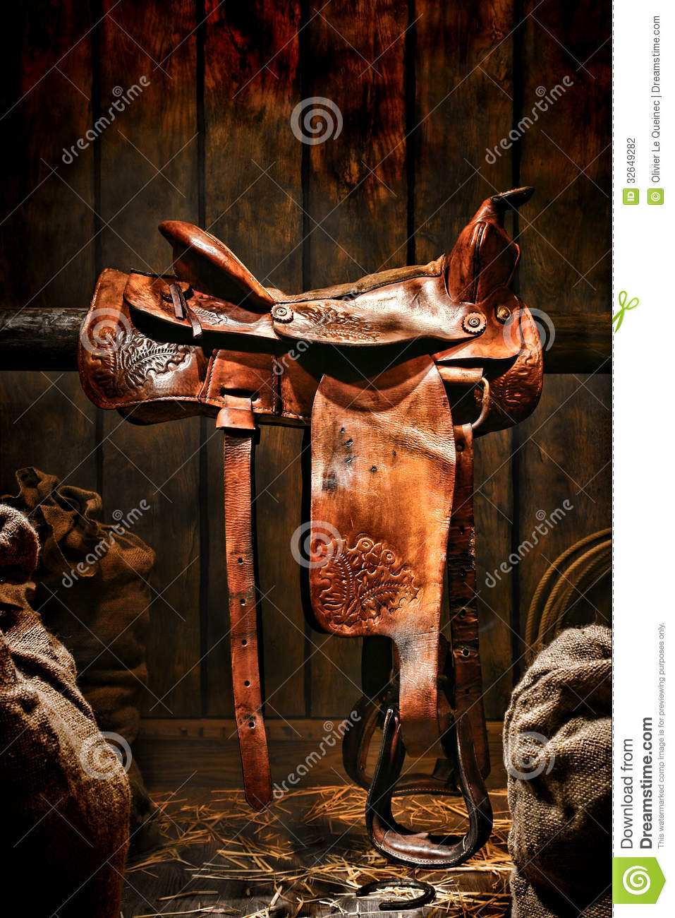 ... brown leather western saddle on a wood rail in an old ranch wood barn