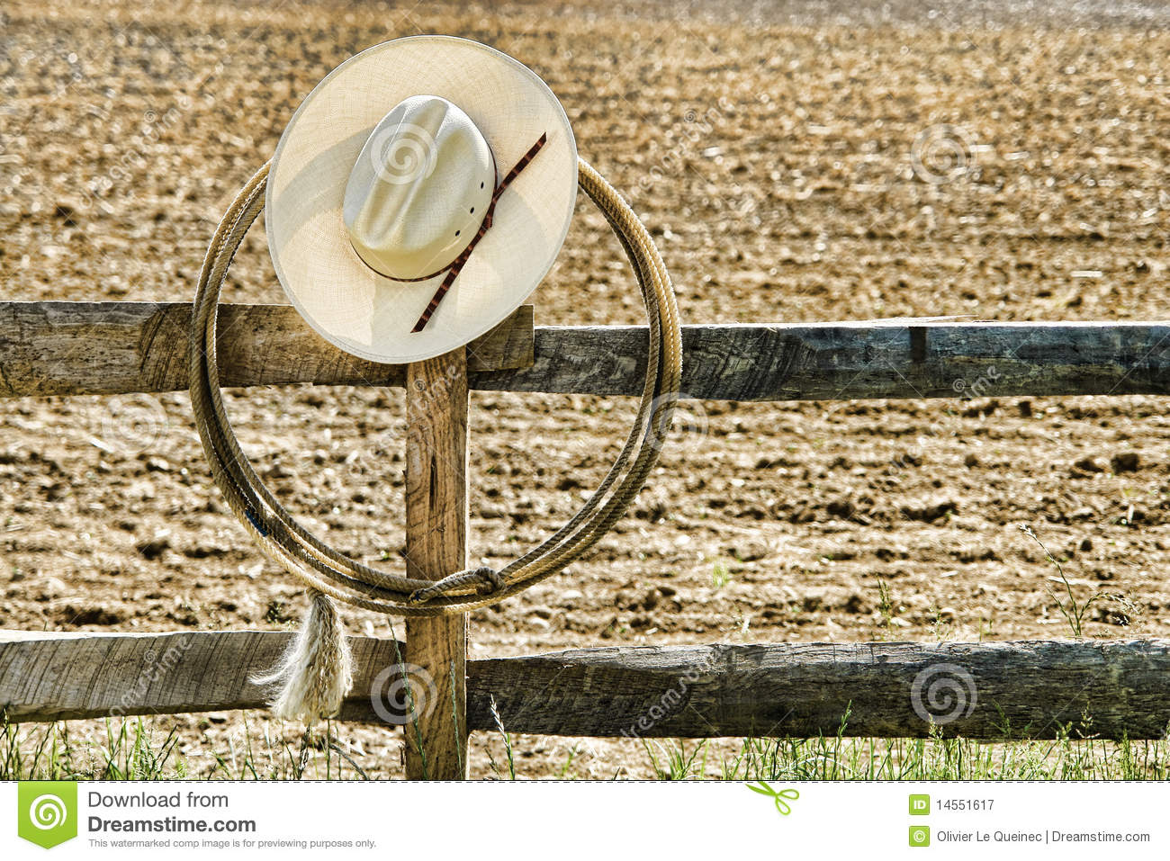 6b5b9401a42 American West rodeo cowboy white straw hat and roping lasso hanging on an old  wood fence post on an agriculture farm field at a Western ranch