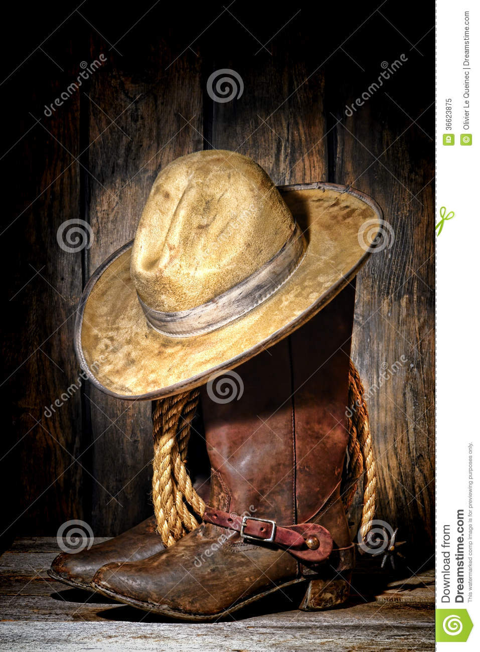 American West rodeo cowboy dirty and used white felt hat atop worn and  muddy leather working rancher boots with vintage spurs and old ranching  rope in an ... 2688dc2c912
