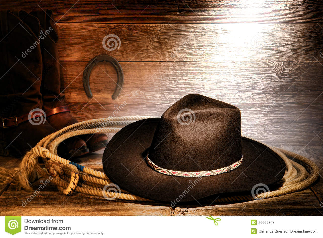 8a924fb6d13c4 American West rodeo cowboy black felt hat on an authentic Western roping  lariat lasso with leather riding boots on weathered wood floor in an old  ranch barn