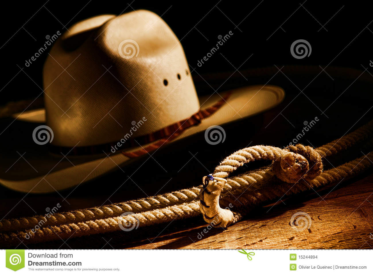 e0915a5fa26a1 American West rodeo cowboy lasso rope and traditional Western white straw  hat in dramatic light with dark shadows