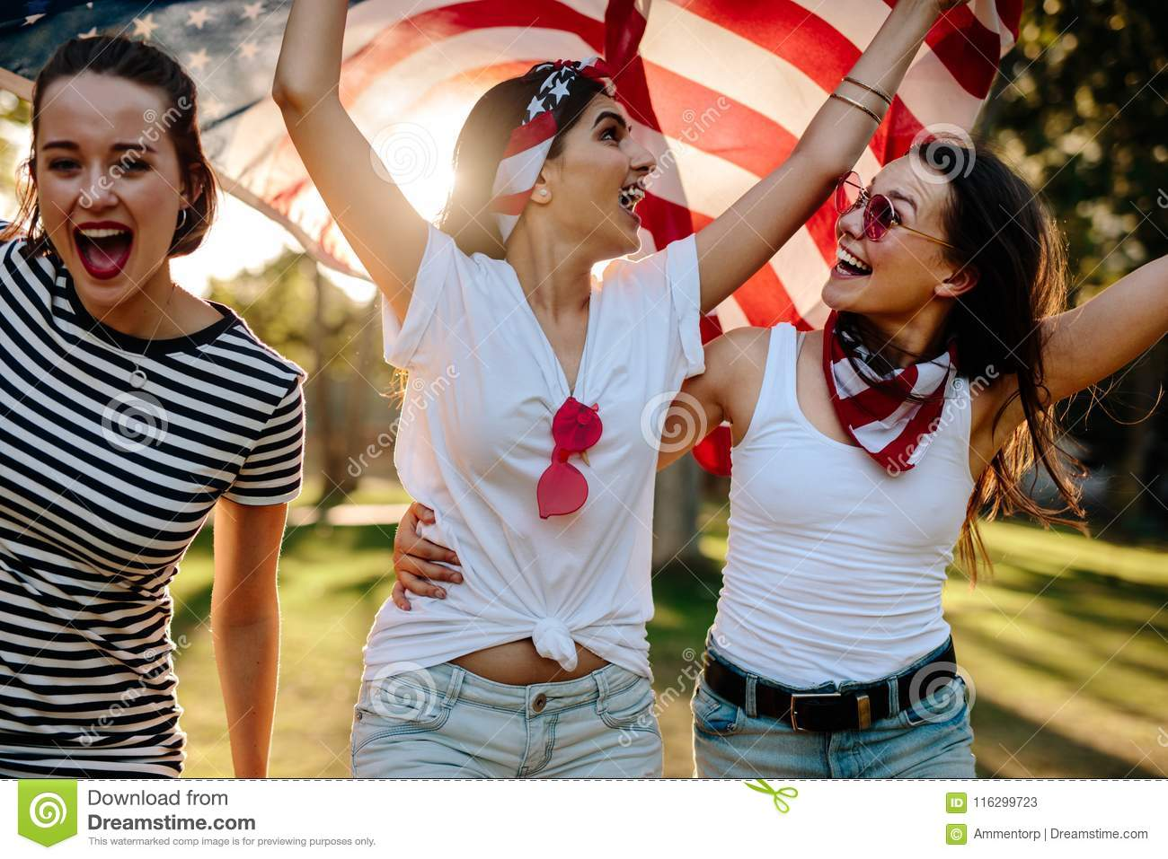 0c48fd8c0f Three young female friends with American flag having fun in the park.  Smiling group of women celebrating 4th of july outdoors.