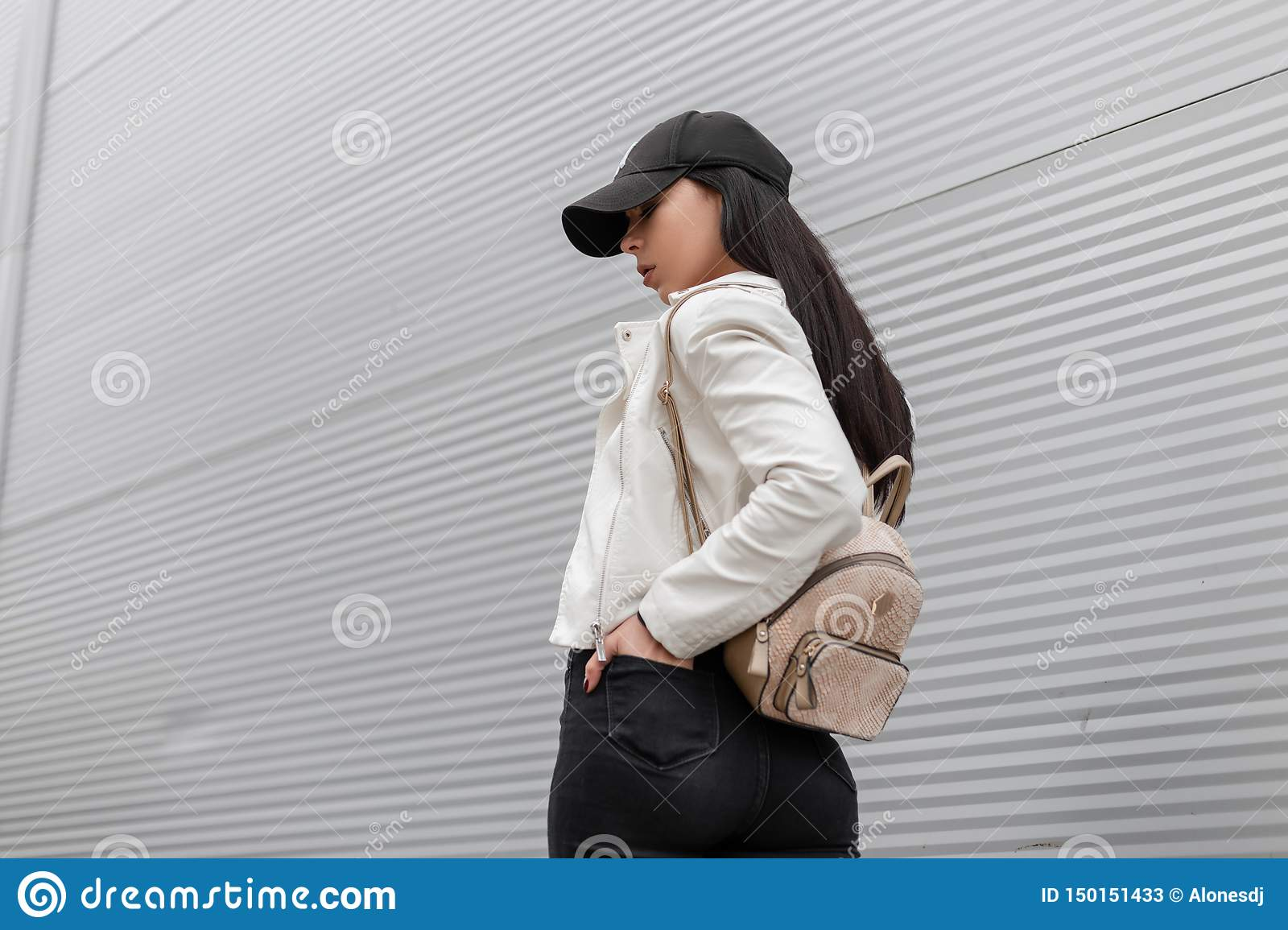 American young woman in a stylish cap with a trendy gold backpack in a vintage white leather jacket traveling along the street