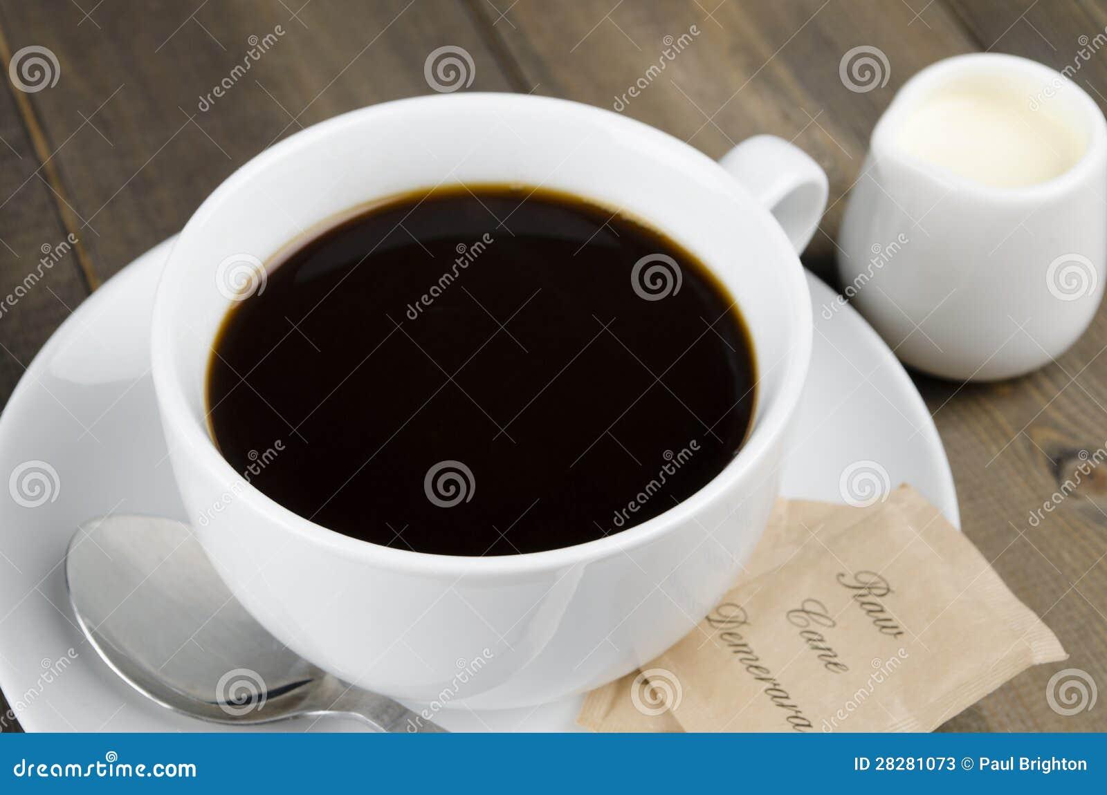 Americano black coffee in a white cup with raw demerara sugar sachets ...