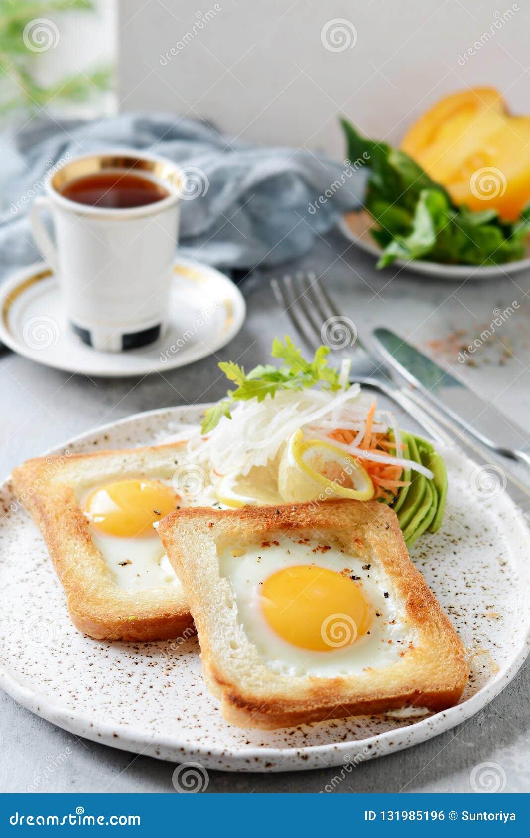 Amerikansk frukost på en platta med stekte ägg i rostat bröd, med tomater, ny daikon, morötter, arugula och espresso stekt ägg
