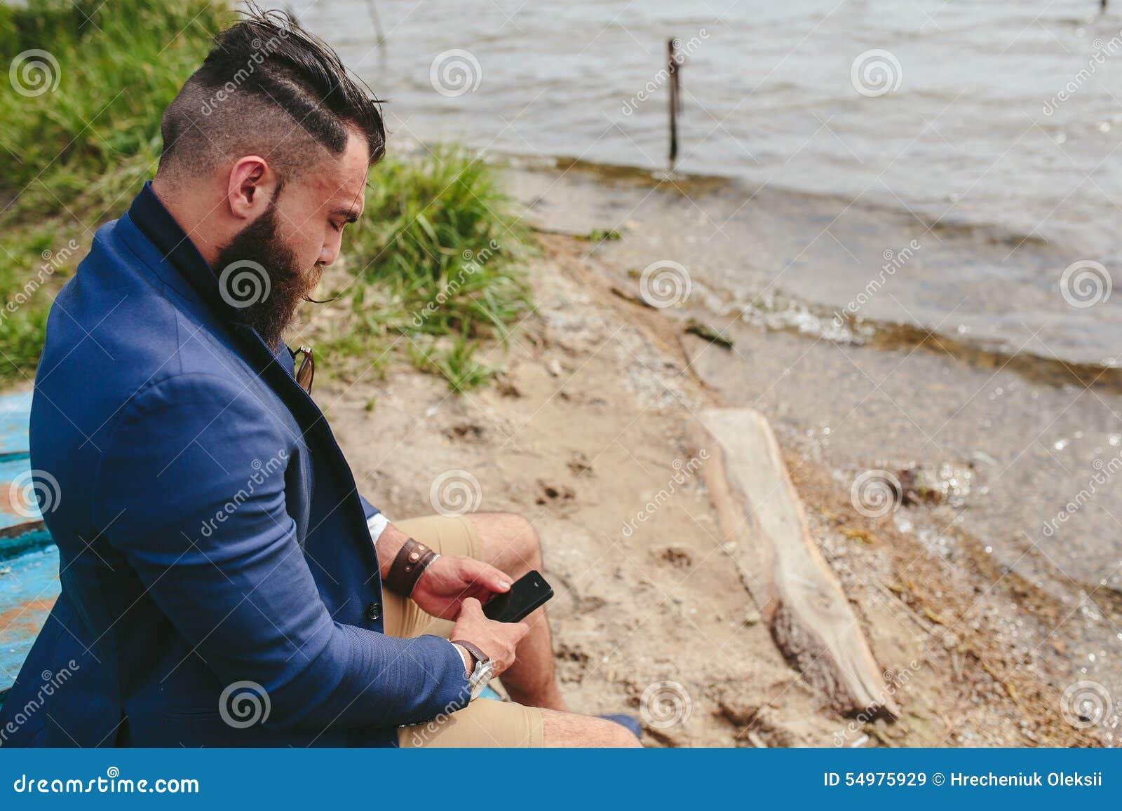 Amerikansk skäggig man som använder telefonen nära floden
