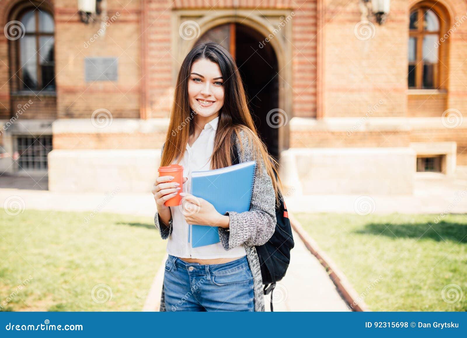 Amerikansk universitetsstudent som ler med kaffe- och bokpåsen på universitetsområde