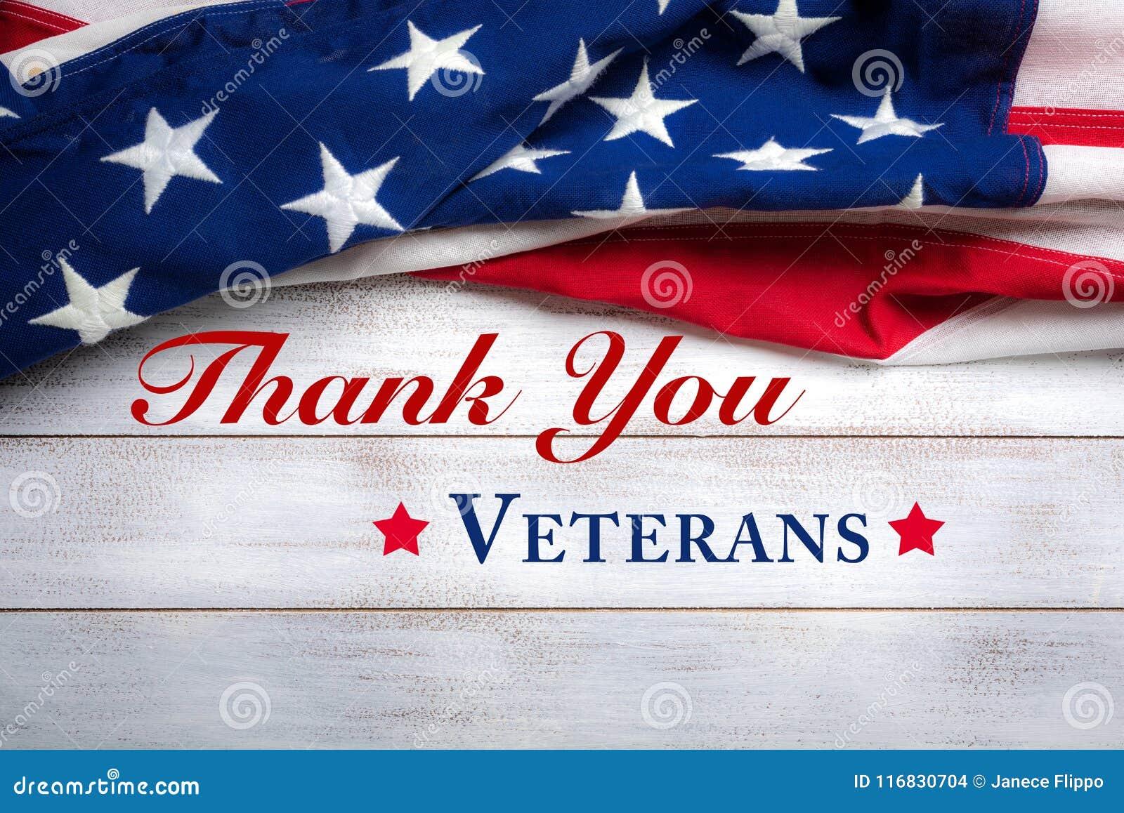 Amerikanska flaggan på en vit sliten träbakgrund med hälsning för dag för veteran` s