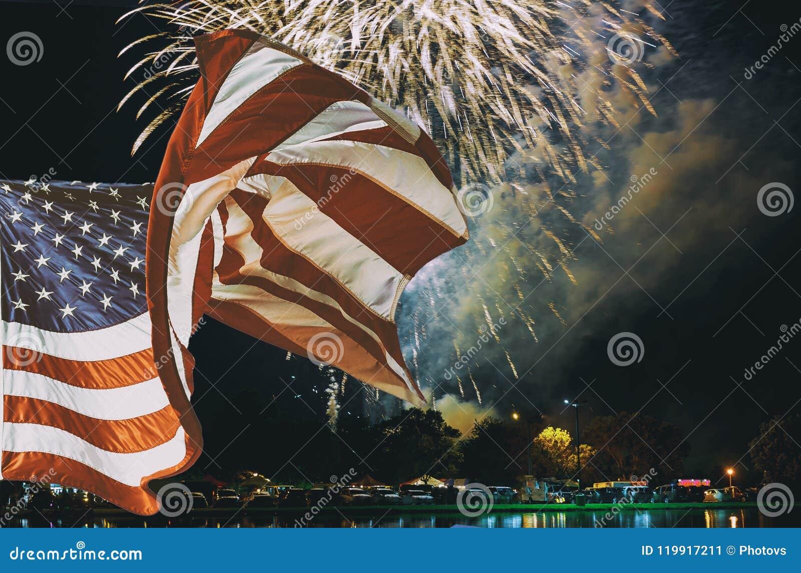 Amerikanska flaggan som vinkar, i att moussera röda fyrverkerier för gräsplangulingberöm över stjärnklar himmel Självständighetsd