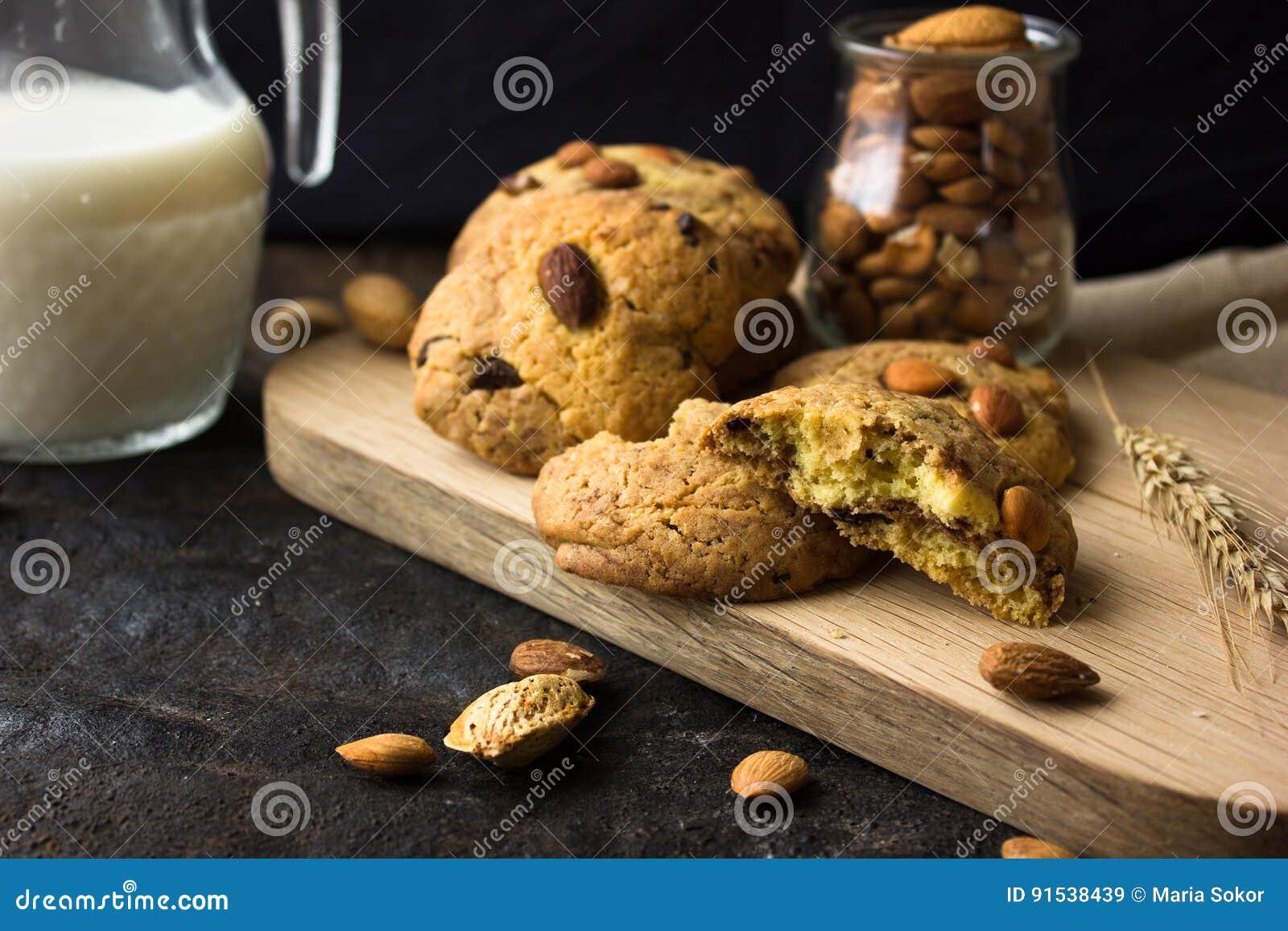 Amerikanska mördegskakakakor med chokladdroppar och en tillbringare av mjölkar och mandlar Mörk grungebakgrund Mystiskt ljust