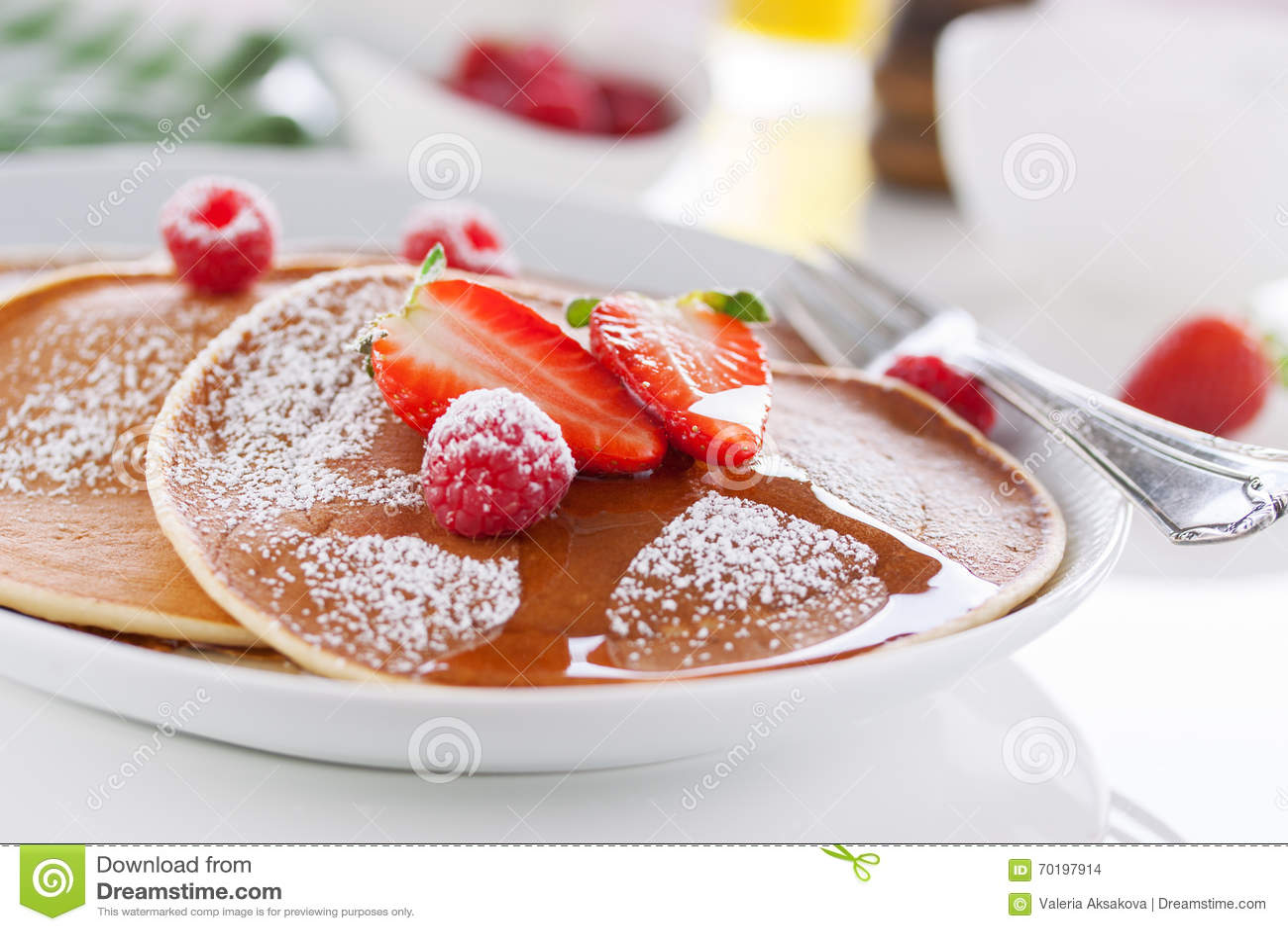 Amerikanska pannkakor för hemlagad kärnmjölk med den nya jordgubben och hallonet på en vit platta