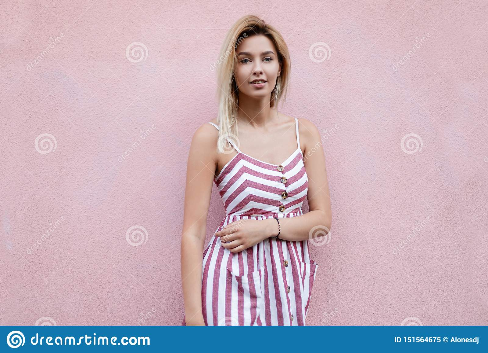 Amerykańska wspaniała młoda kobieta z blondynem w eleganckich pasiastych menchii smokingowy pozuje stać blisko różowego rocznika