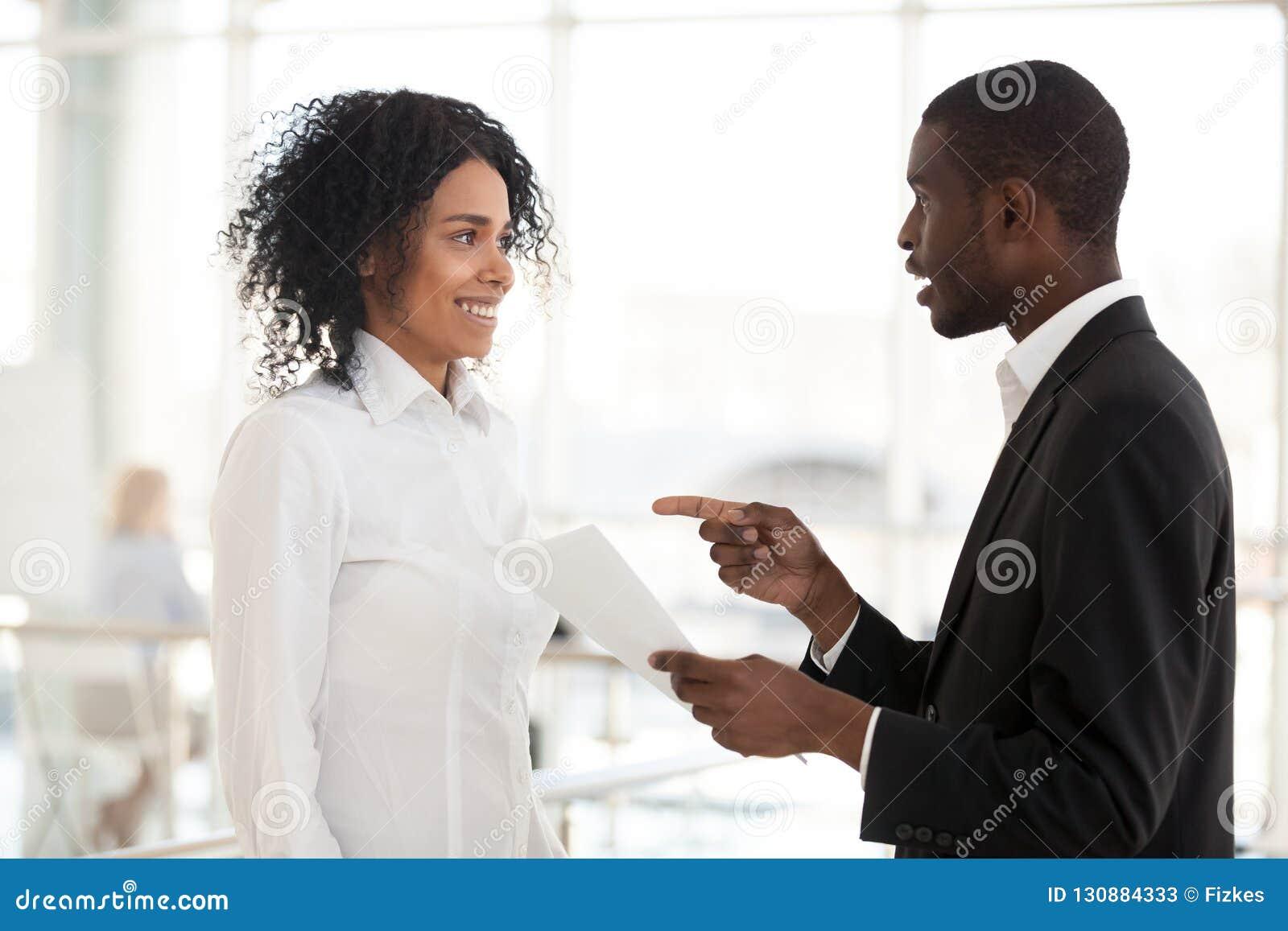 Amerykanin Afrykańskiego Pochodzenia biznesmen promuje z podnieceniem żeńskiego spotkania w h
