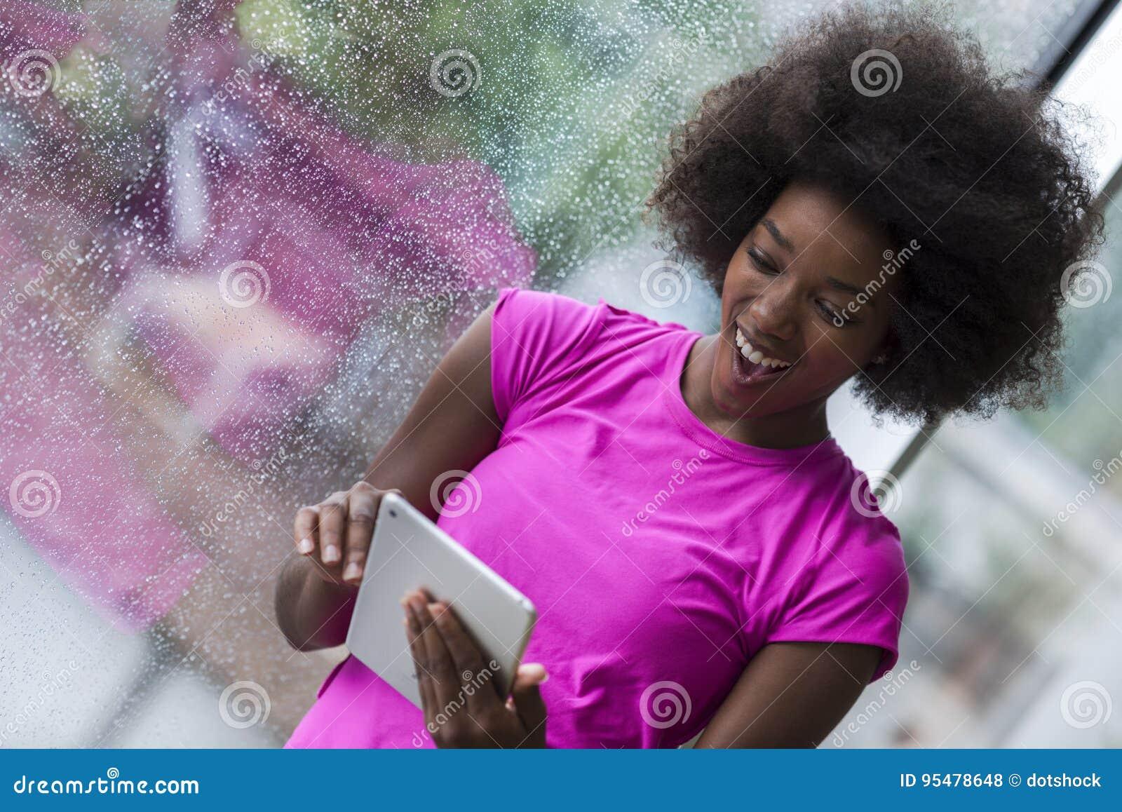 Amerykanin afrykańskiego pochodzenia kobieta używa pastylkę