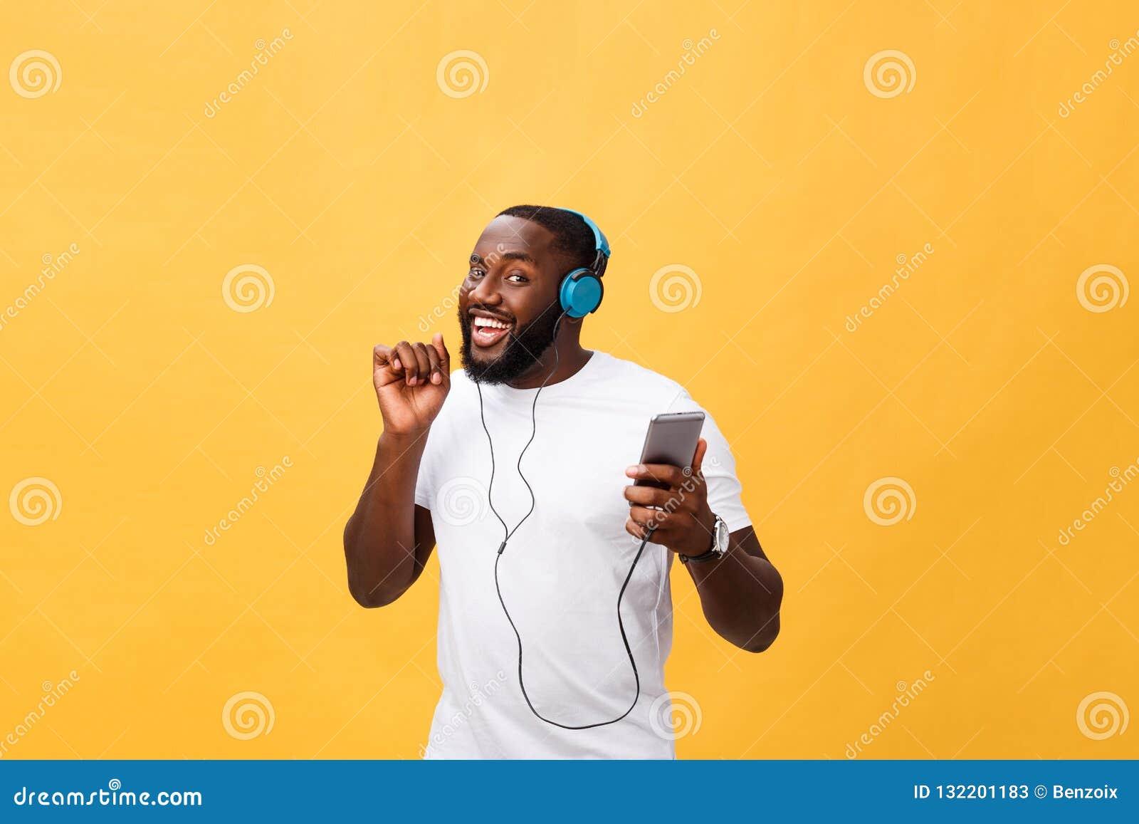 Amerykanin Afrykańskiego Pochodzenia mężczyzna z hełmofonami słucha i tanczy z muzyką Odizolowywający na żółtym tle