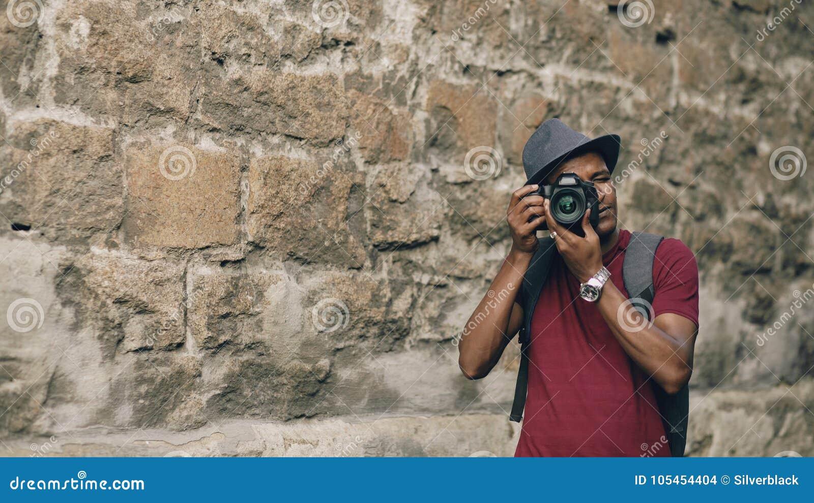 Amerykanin afrykańskiego pochodzenia szczęśliwa turystyczna bierze fotografia na jego dslr kamerze Młody człowiek stoi blisko sła
