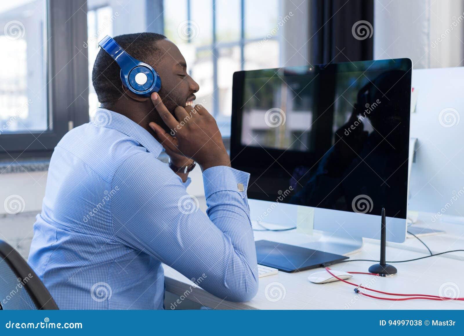 Amerykanina Afrykańskiego Pochodzenia biznesmen Słucha muzyka Z hełmofonami W Nowożytnej Coworking przestrzeni, Dorosły Biznesowy