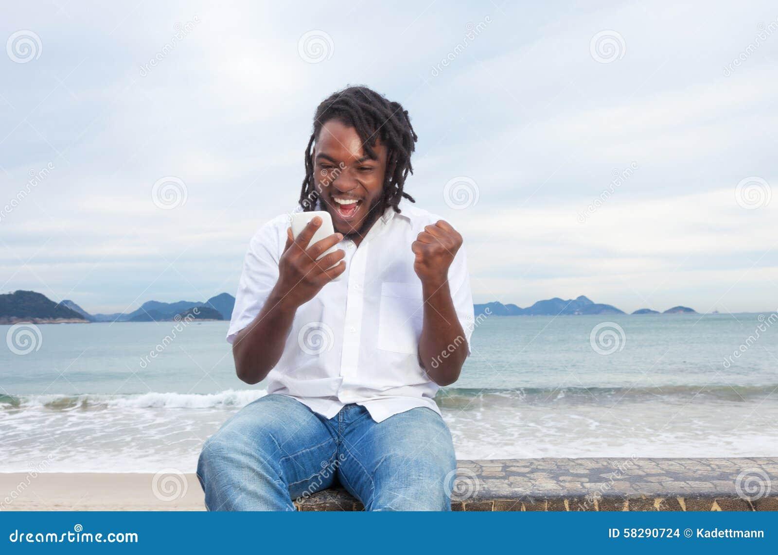 Amerykanina afrykańskiego pochodzenia facet z dreadlocks i białym koszulowym odbiorczym dobre em wieści