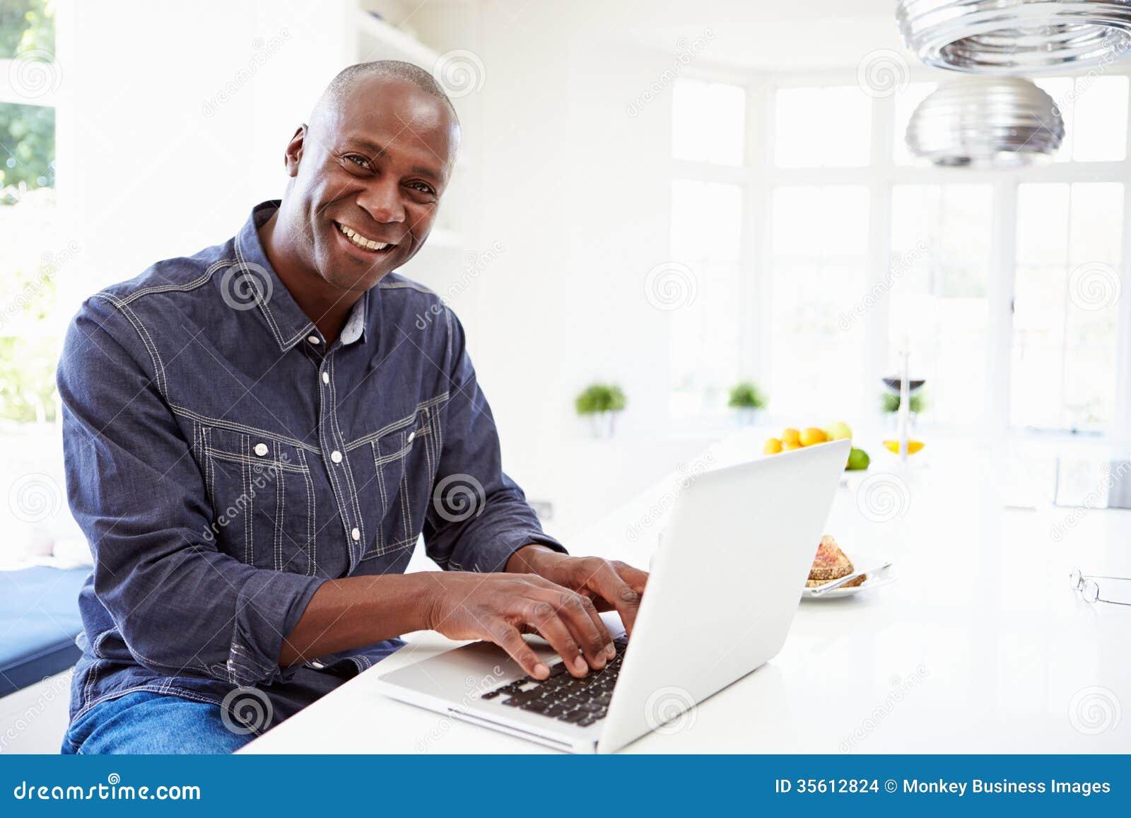 Amerykanina Afrykańskiego Pochodzenia mężczyzna Używa laptop W Domu