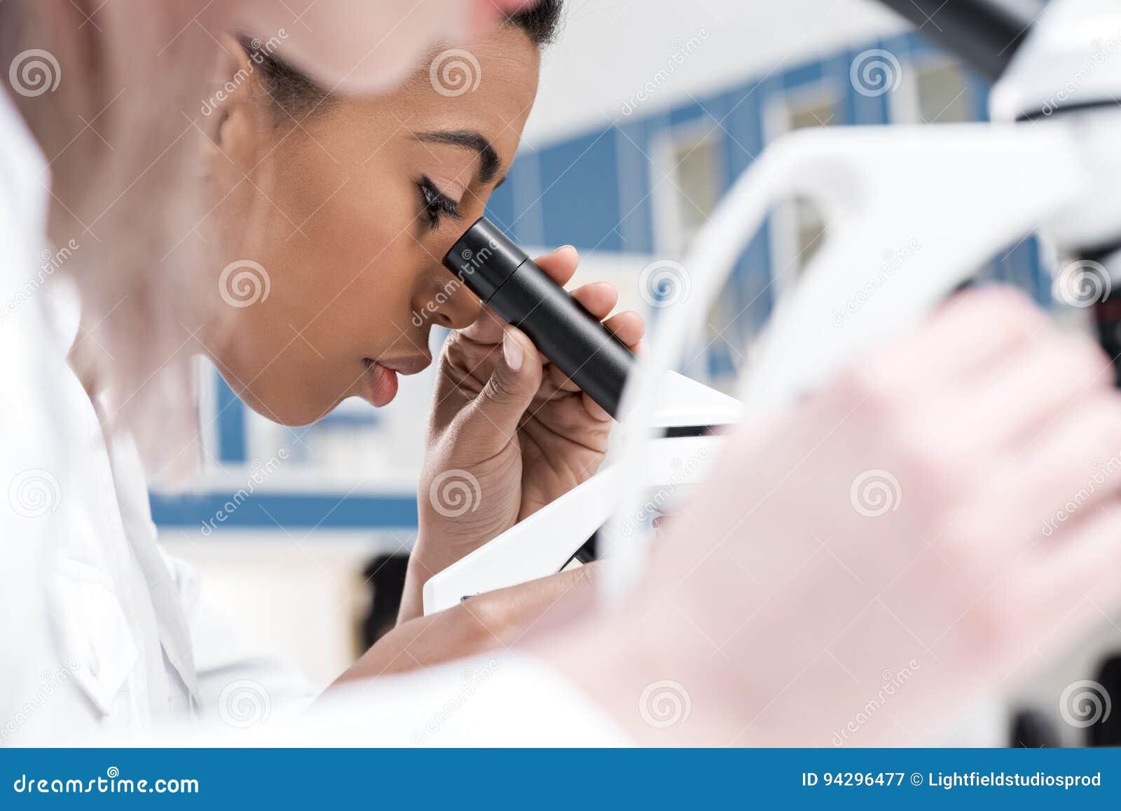Amerykanina afrykańskiego pochodzenia naukowiec pracuje z mikroskopem w chemicznym lab