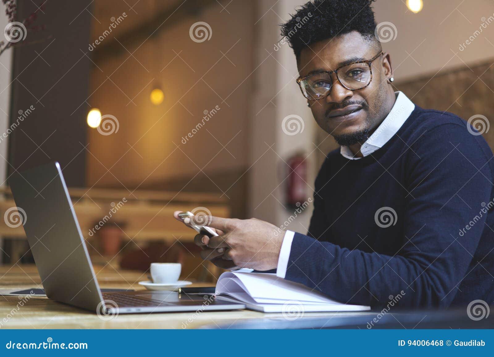 Amerykanina afrykańskiego pochodzenia uczeń szkoła biznesu w ciemnym pulowerze i białej koszula