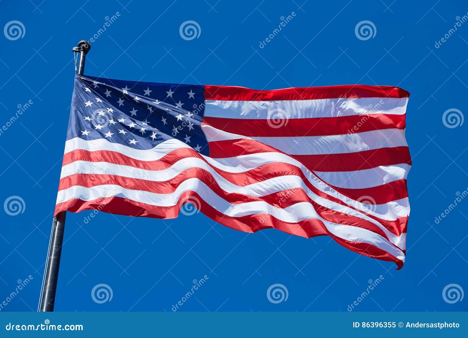 Amerykanina lub usa flaga w wiatrze z flagpole na niebieskim niebie