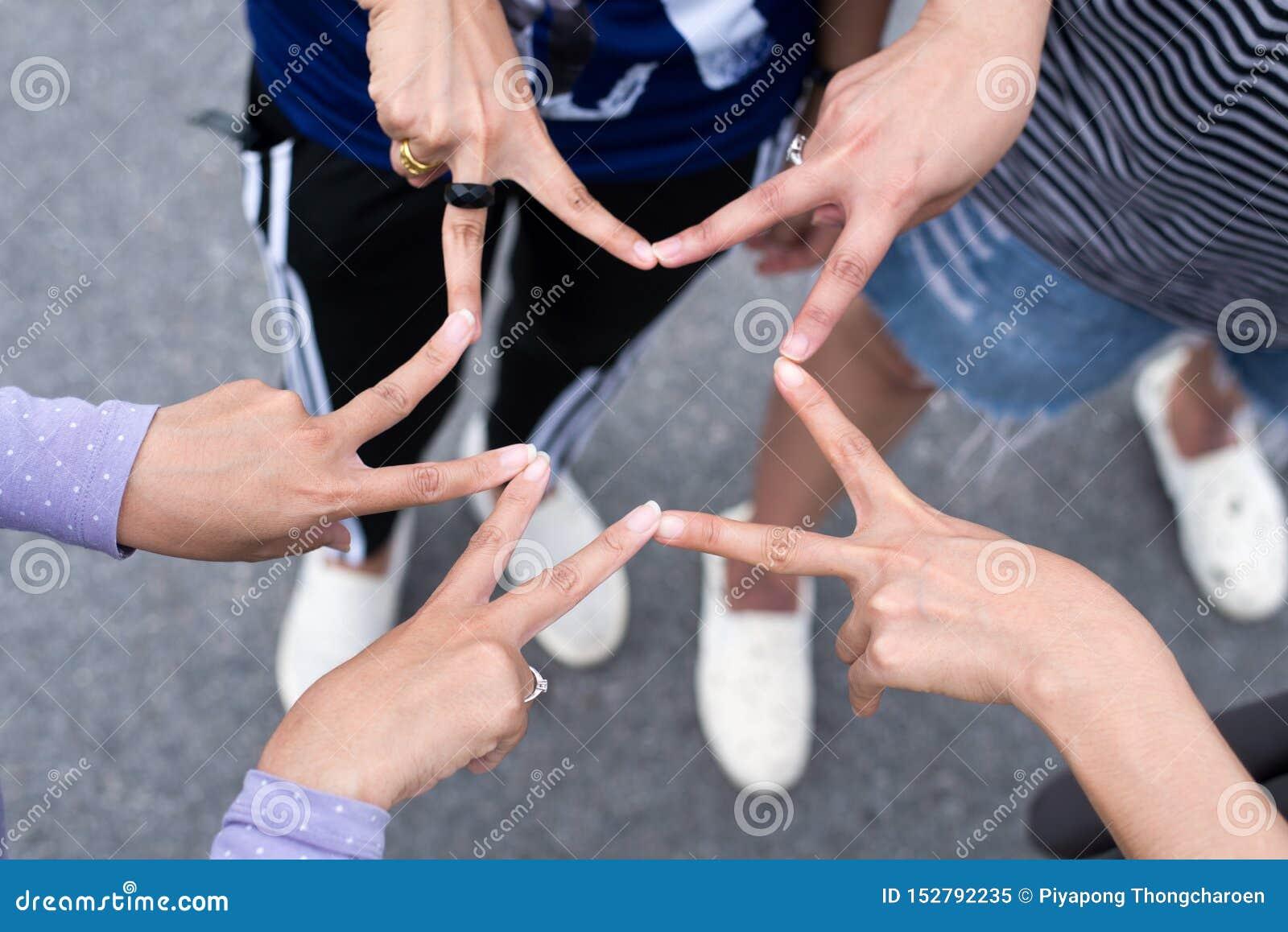 Ami de femme mettant avec les mains et le signe d étoile de posture de doigt et montrant ensemble, concept réussi de travail d éq