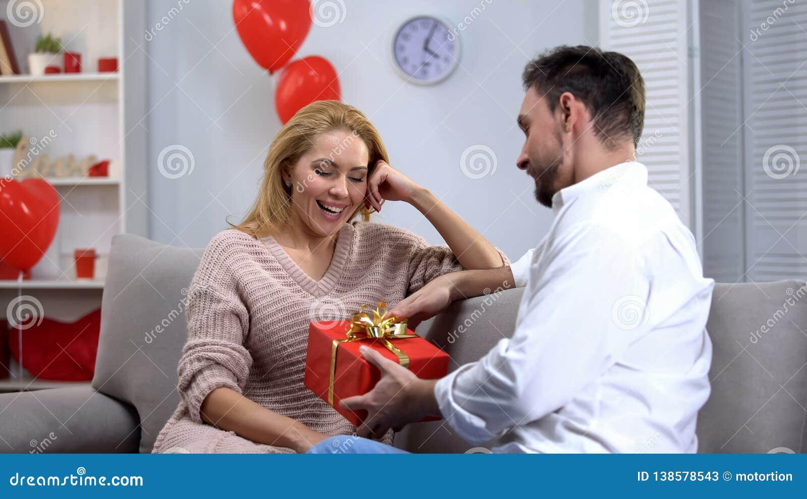 Ami donnant le cadeau heureux étonné de dame pour le jour de valentines de St, couple heureux