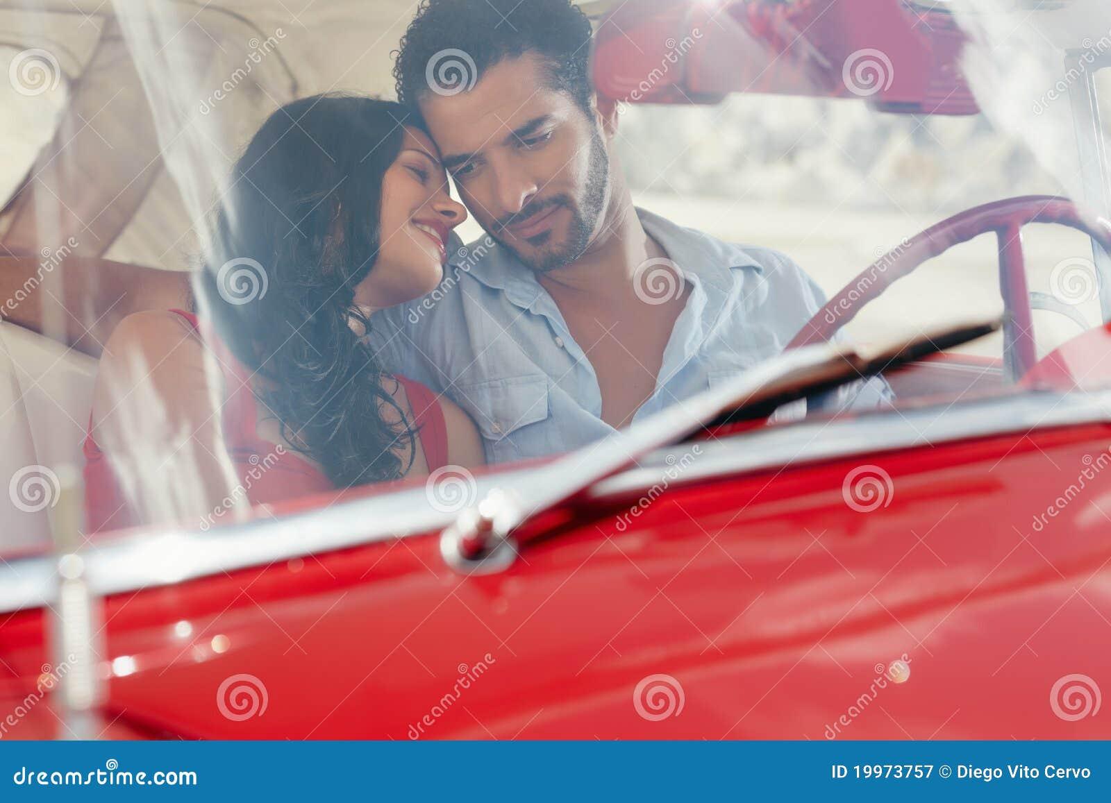Amica e ragazzo che flirtano in vecchia automobile rossa