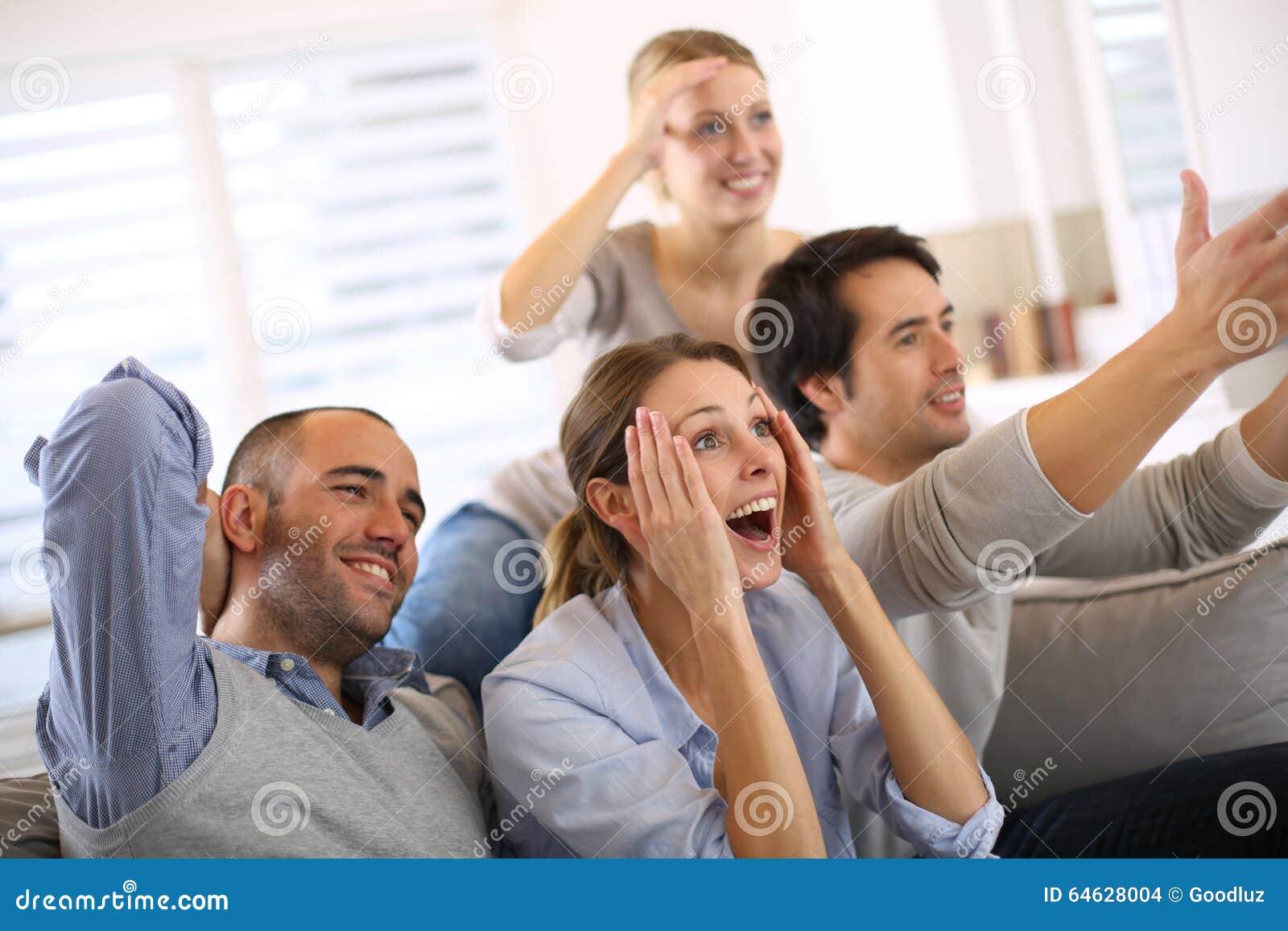 Amici allegri che guardano partita di football americano a casa