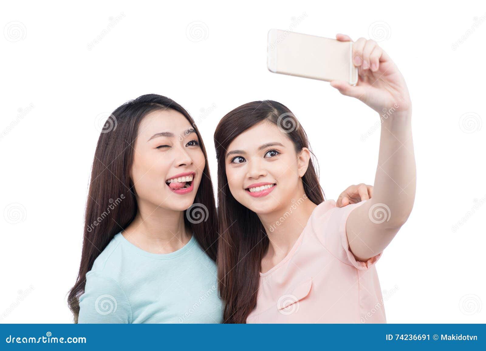 Amici asiatici felici della donna che prendono un autoritratto con un pho delle cellule