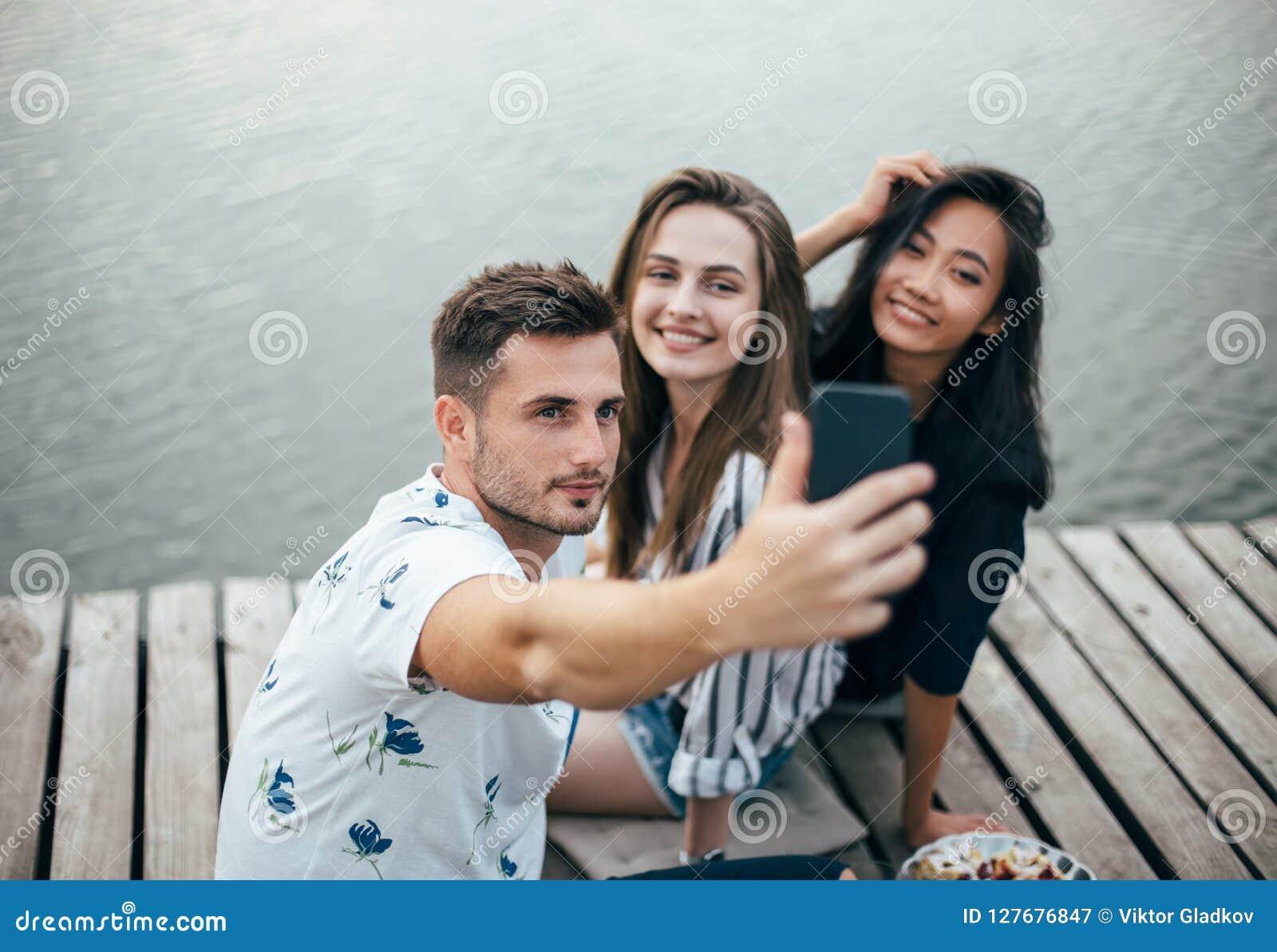 Amici che fanno selfie che si siede sul pilastro con il fondo del lago mentre