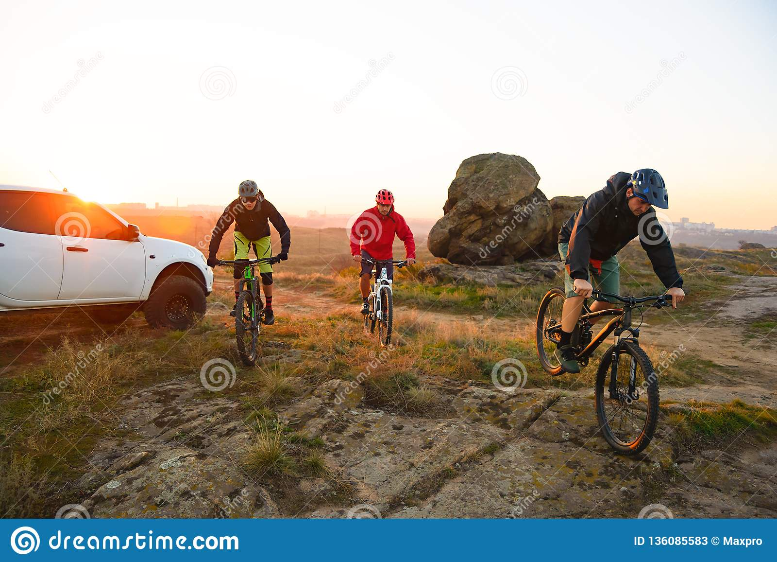 Amici che guidano le bici nelle montagne davanti al camion di Off Road della raccolta al tramonto Concetto di viaggio e di avvent