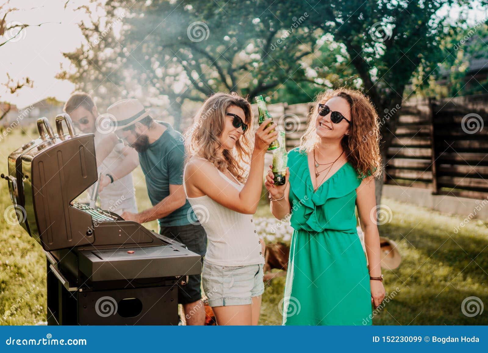 Amici che hanno un partito del barbecue, ragazze che ridono e che sorridono, beventi e cucinanti