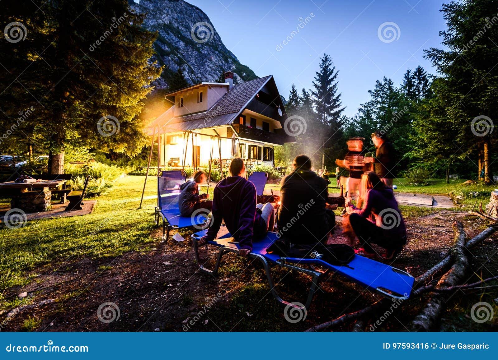Amici che si siedono intorno al falò nel legno e nella casa di vacanza