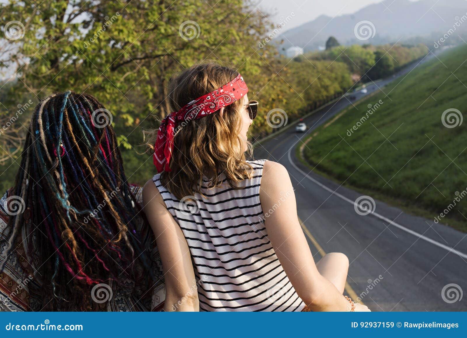 Amici che si siedono sul tetto di Van Traveling Road Trip