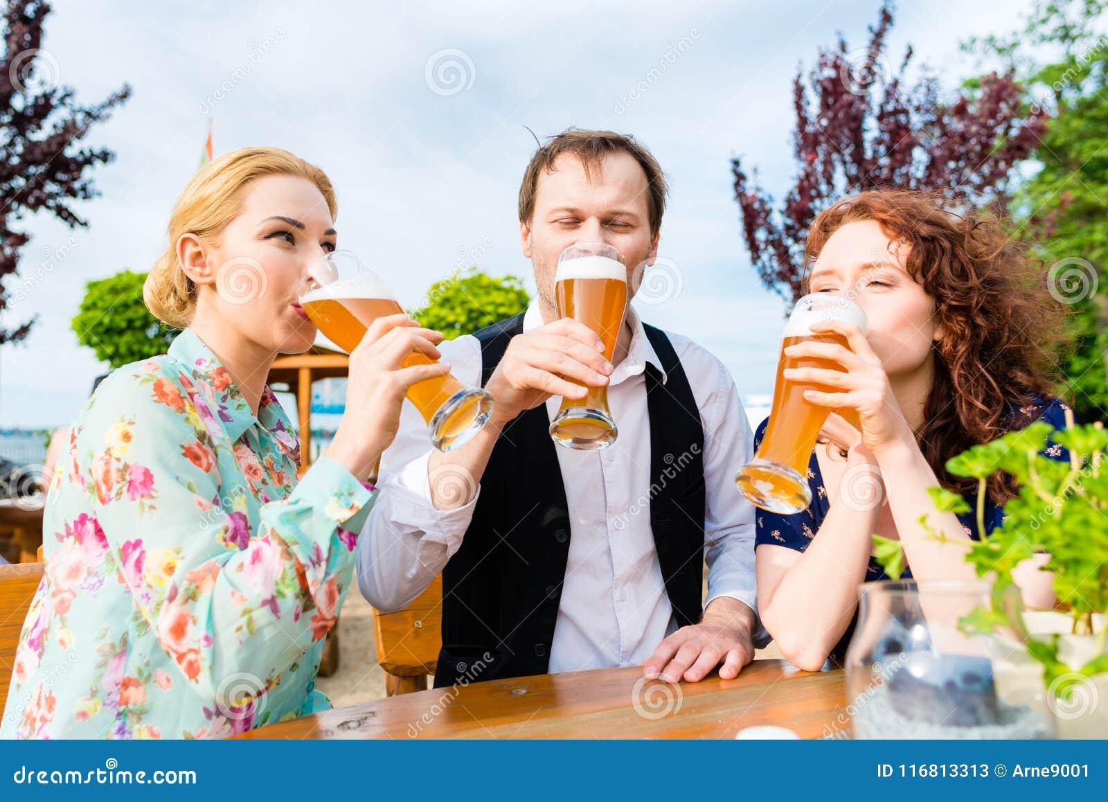 Amici che tostano con la birra nel ristorante del giardino