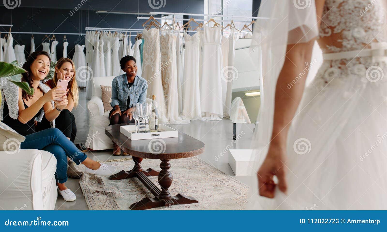 Amici con la sposa nella stanza adatta del vestito nuziale