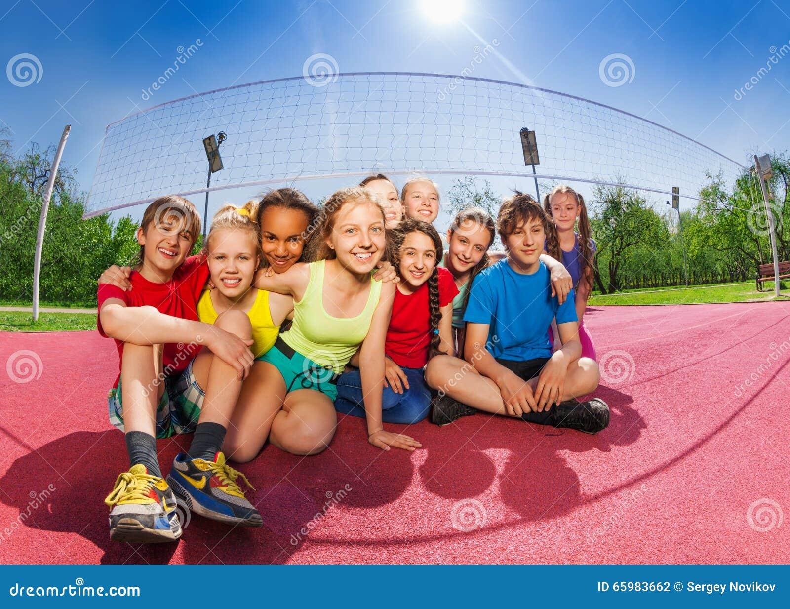 Amici felici che si siedono sulla corte del gioco di pallavolo