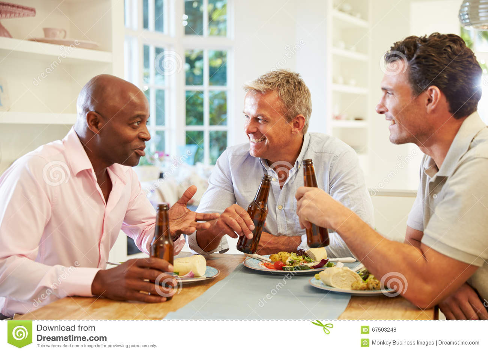 Amici maschii maturi Sit At Table Drinking Beer e mangiare