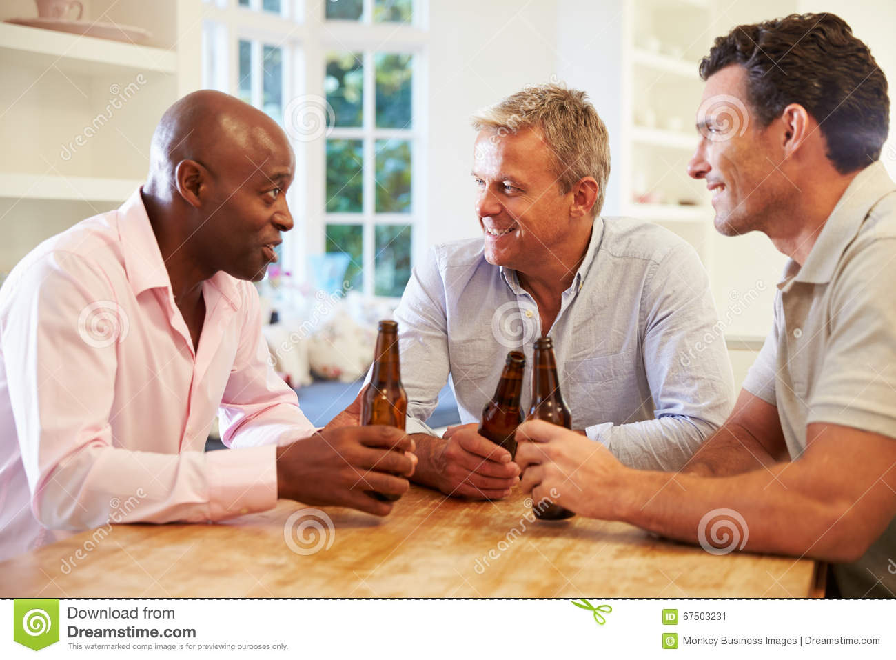 Amici maschii maturi Sit At Table Drinking Beer e parlare