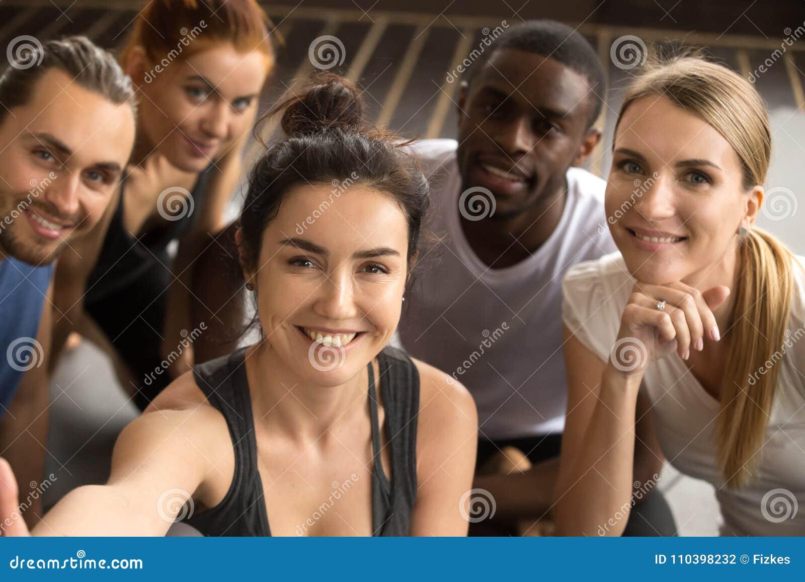 Amici multirazziali sportivi che prendono la tenuta del selfie del gruppo che guarda a