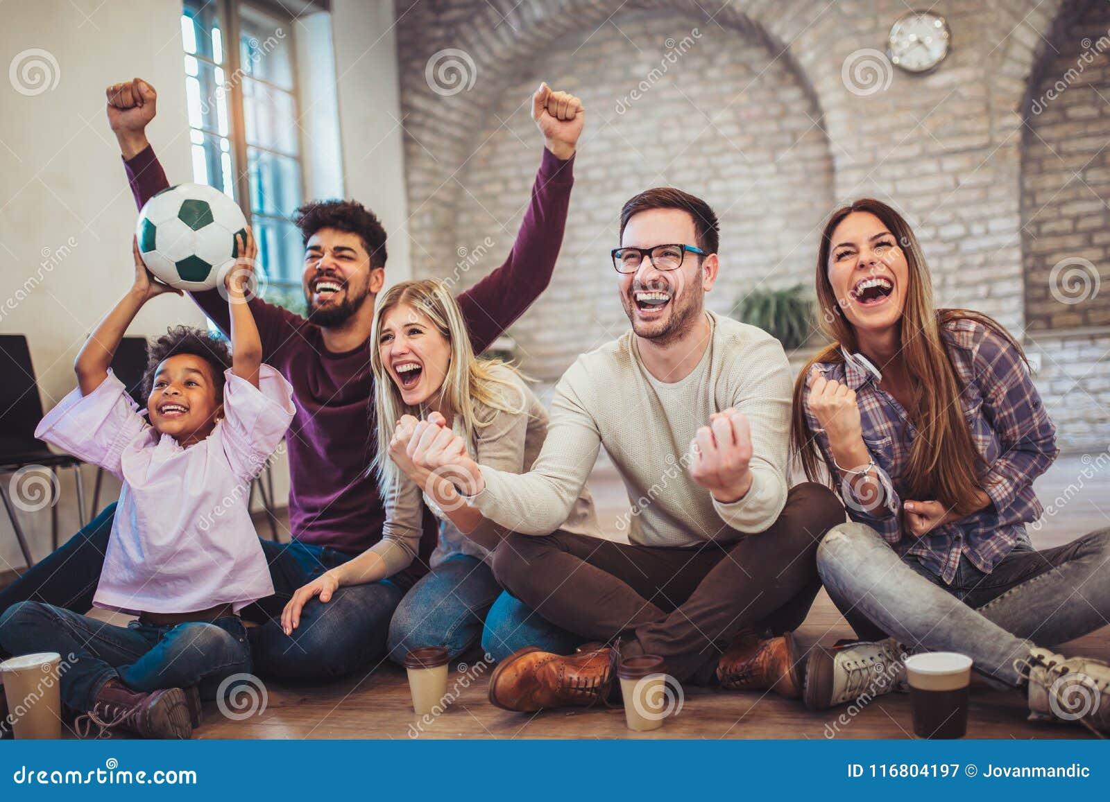 Amici o tifosi felici che guardano calcio sulla TV e che celebrano vittoria