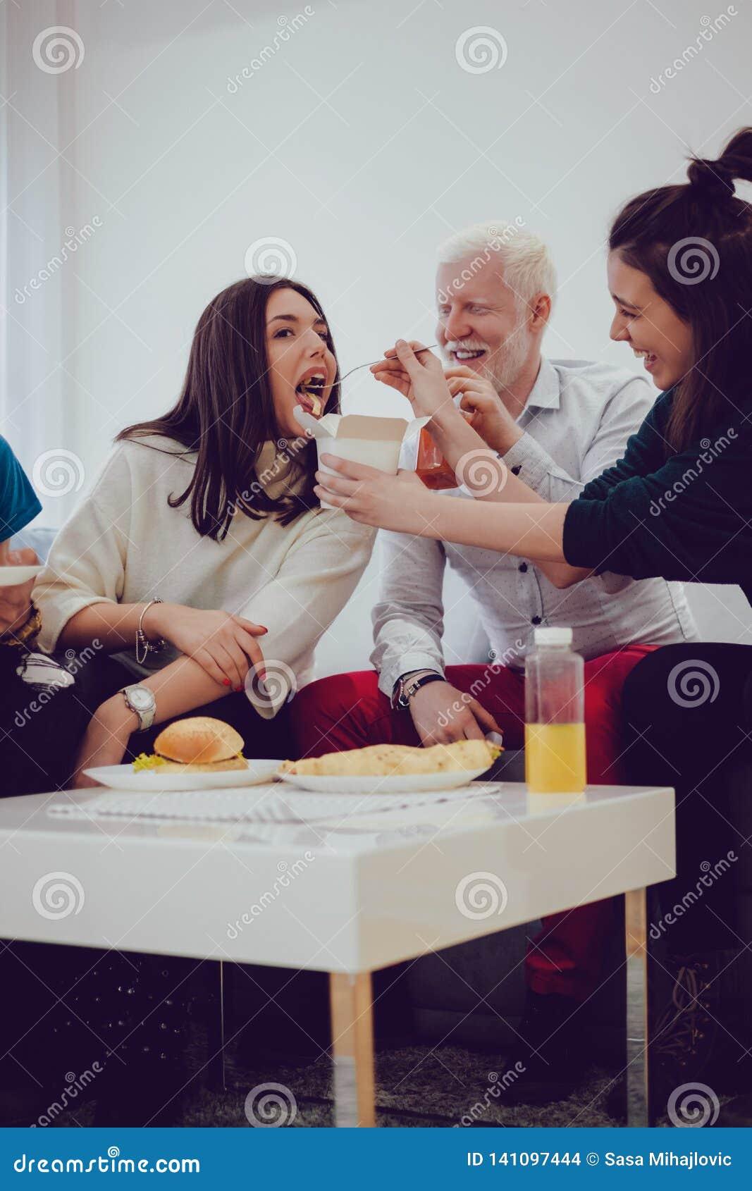 Amiga de alimentação da menina com massa quando os amigos sorrirem