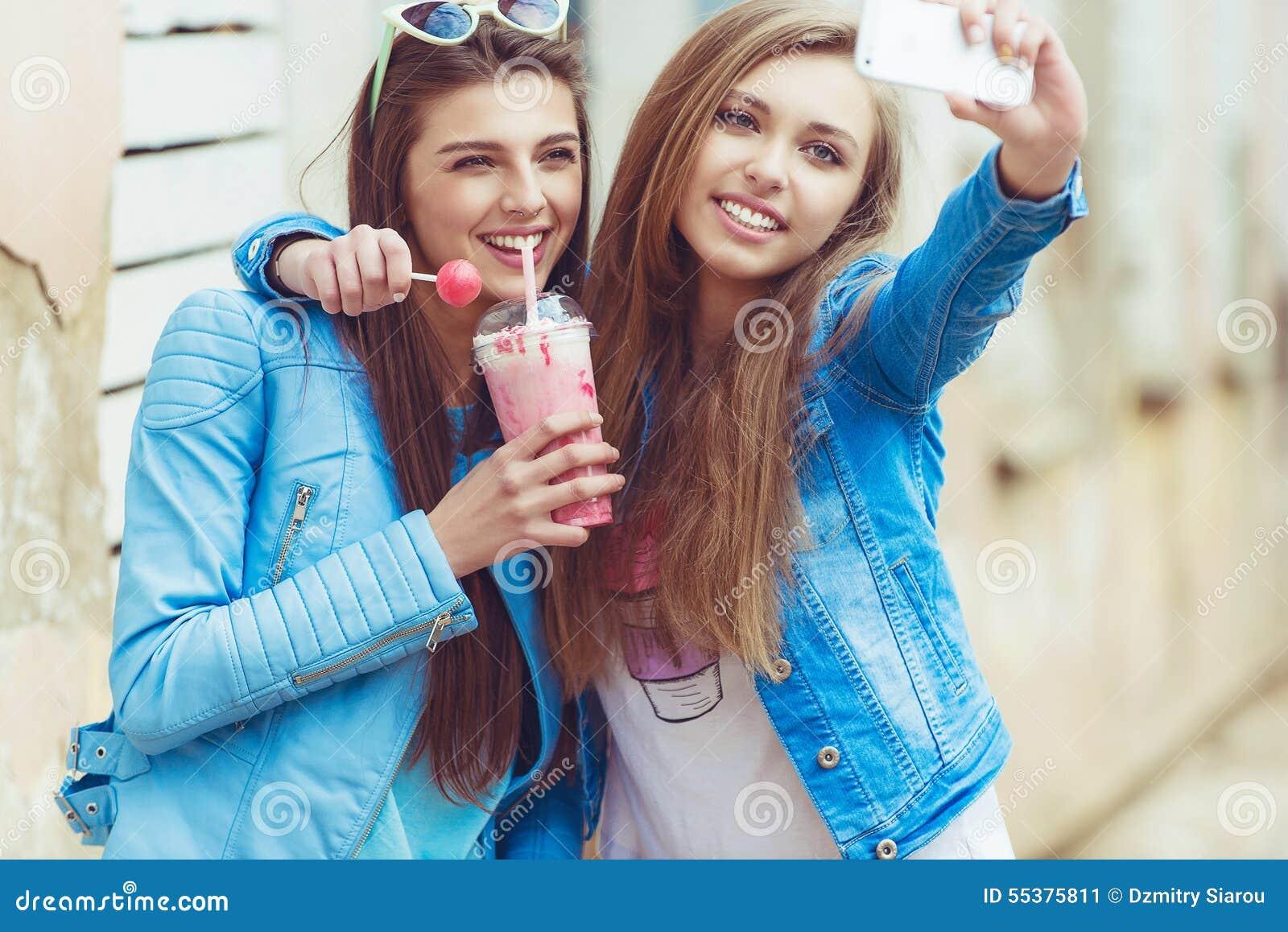 Amigas do moderno que tomam um selfie na cidade urbana