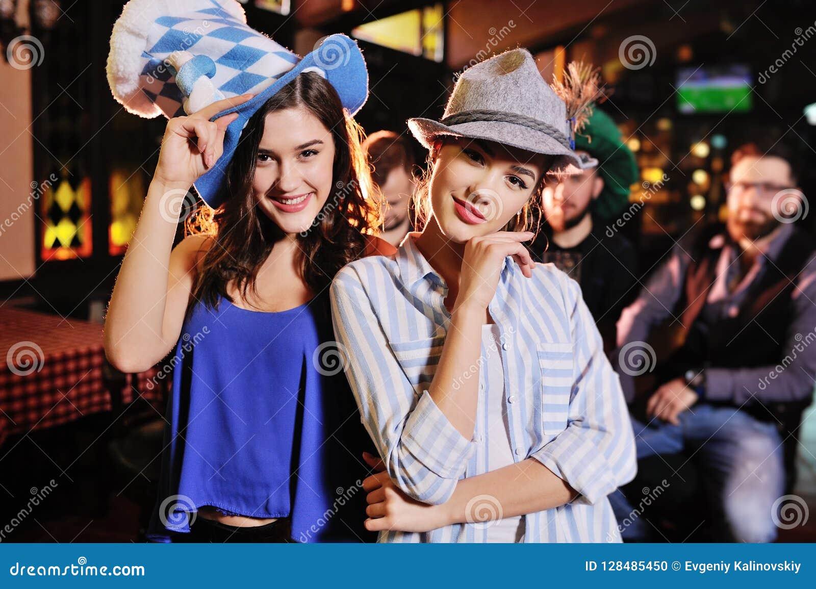 Amigas novas bonitos em chapéus bávaros que sorriem no fundo da barra durante a celebração do Oktoberfest