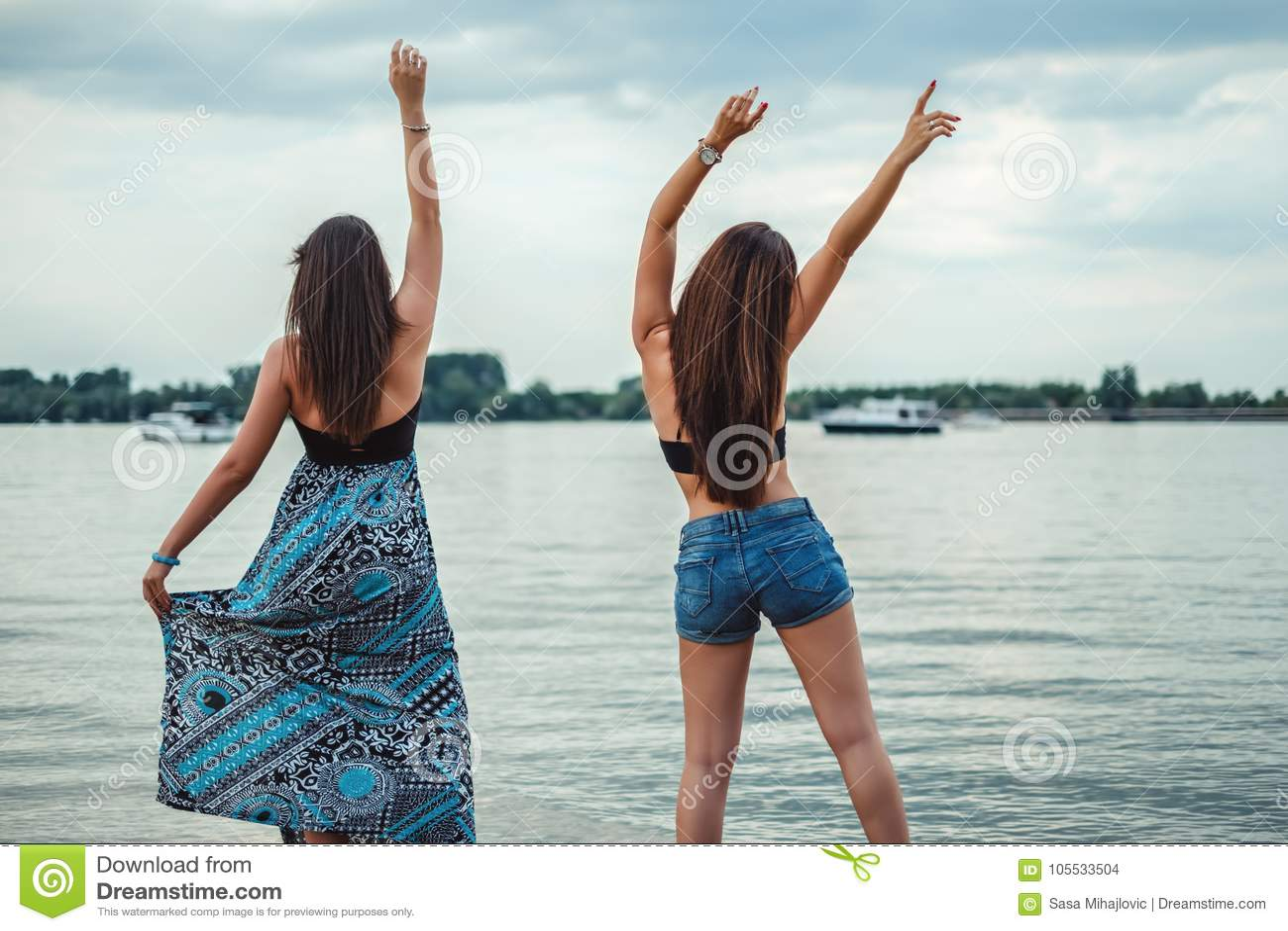 Amigas que dançam e que acenam na praia