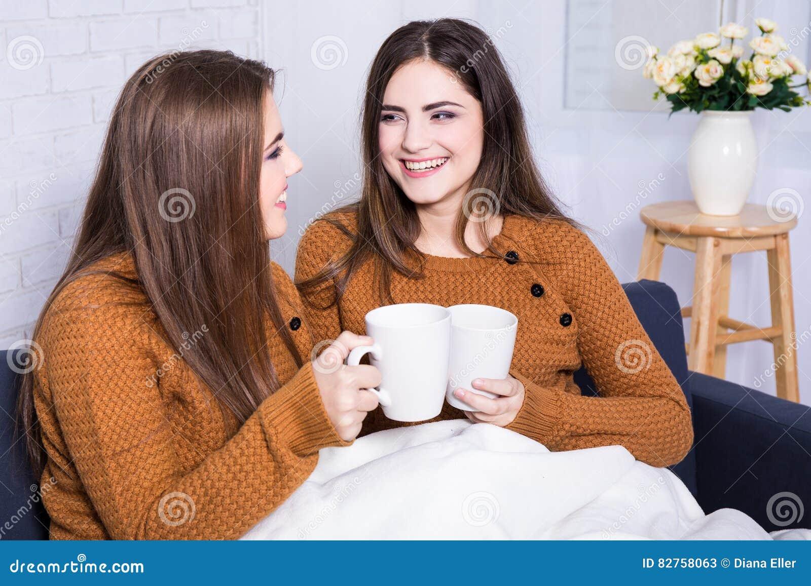 Amigas que falam e que bebem o café ou o chá que sentam-se no sofá a
