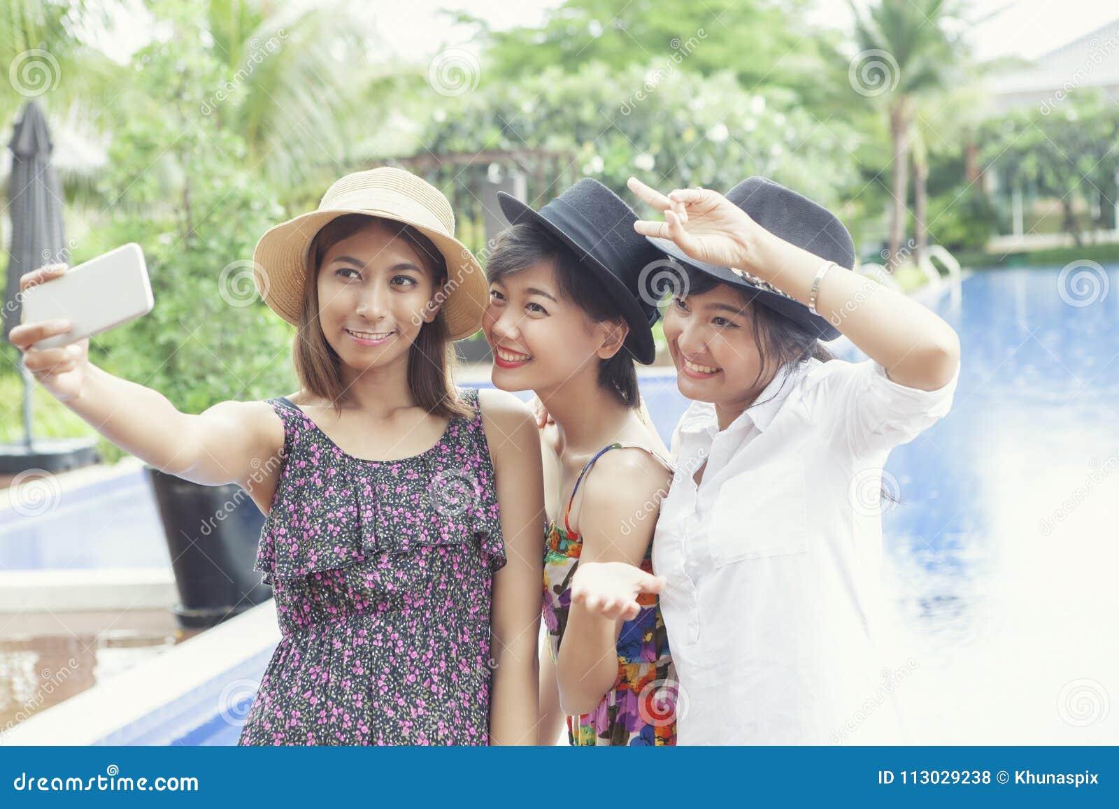 Amigo asiático de una mujer más joven que toma fotografía por el hap elegante del teléfono
