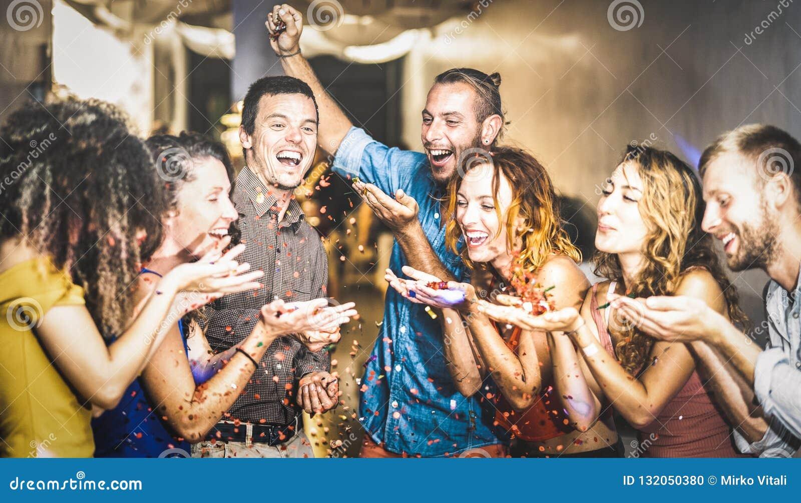 Amigo feliz multirracial que tem o divertimento na celebração da véspera de Ano Novo